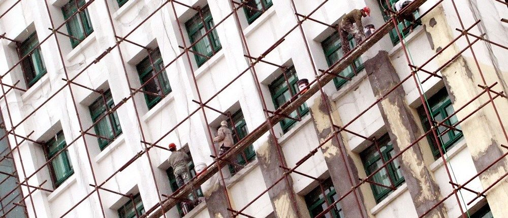 Workers painting facade of building