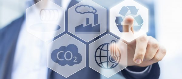 A man pushing the recycling icon on a screen with many different symbols representing sustainability - CO2 emissions and the impact of the construction sector on climate change