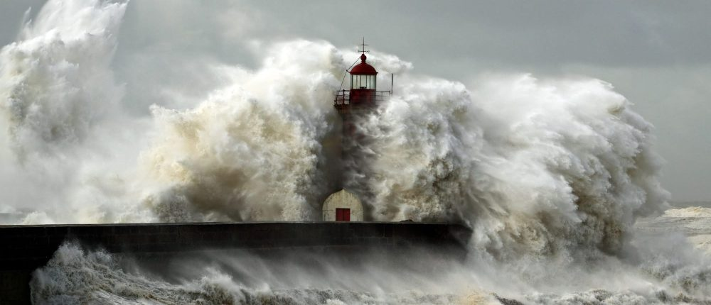 Lighthouse on shore in the middle of giant waves