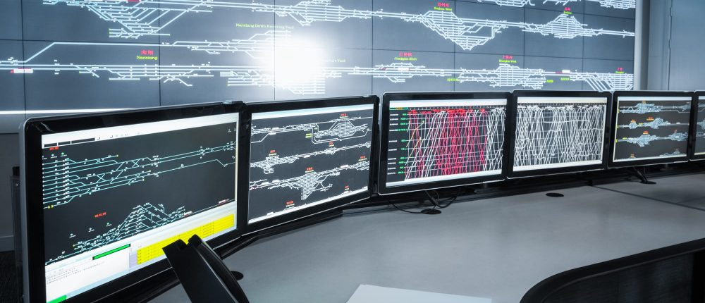 A control room with large and small screens illustrating the operations and maintenance phase of construction